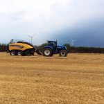 New Holland Tractor and Baler in field